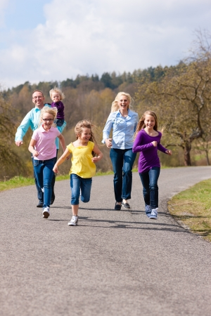 Family (mother, father and four children) is running outdoors in spring Stock Photo - 14727935