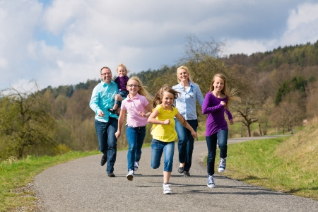 familiy: Family (mother, father and four children) is running outdoors in spring Stock Photo