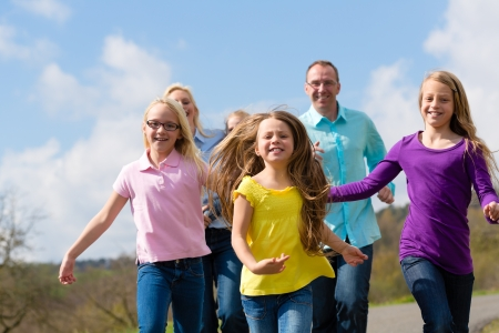 Family (mother, father and four children) is running outdoors in spring Stock Photo - 14727660