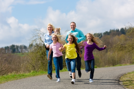 Family (mother, father and four children) is running outdoors in spring photo