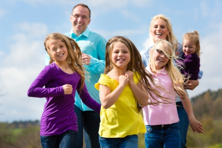 Family (mother, father and four children) is running outdoors in spring Stock Photo - 14727663