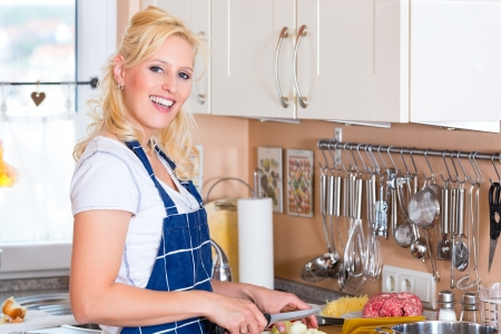 Young Housewife is cooking and chopping onions for lunch or dinner Stock Photo - 14727553