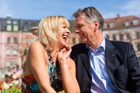 Mature or senior couple sitting on a bench during spring in the city and enjoy the sun photo