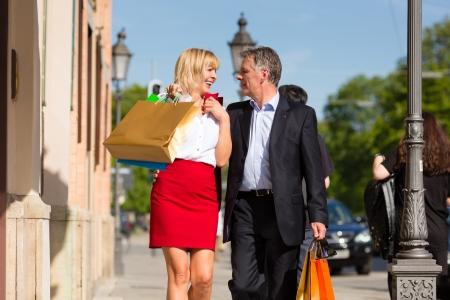 senioren wandelen: Oudere of senior paar wandeling door de stad met boodschappentassen in het voorjaar op een zonnige dag