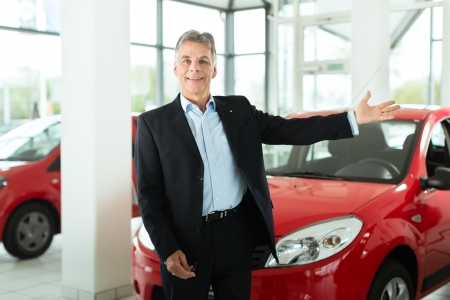 Mature single man with red auto in light car dealership, he is obviously buying a car or is a car dealer photo