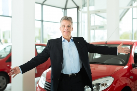 Mature single man with red auto in light car dealership, he is obviously buying a car or is a car dealer Stock Photo - 14725135