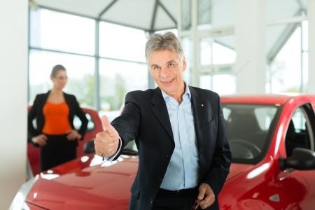 car dealer: Mature single man with red auto in light car dealership with a female customer, a young woman, he is obviously buying a car or is a car dealer