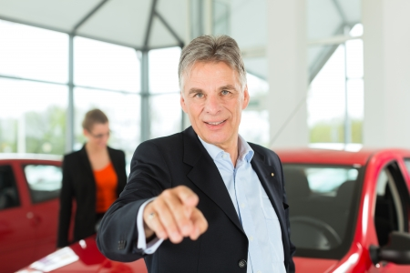 Mature single man with red auto in light car dealership with a female customer, a young woman, he is obviously buying a car or is a car dealer photo