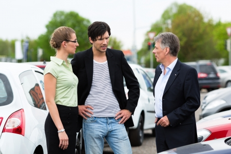 car dealer: Mature car dealer and young couple standing on parking place at dealership in front of cars