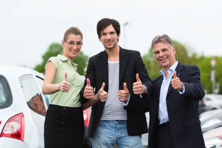 Mature car dealer and young couple standing on parking place at dealership in front of cars Stock Photo - 14725148