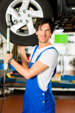 service lift: Young man in blue overall - mechanic - working with lamp on jacked car in a service station Stock Photo