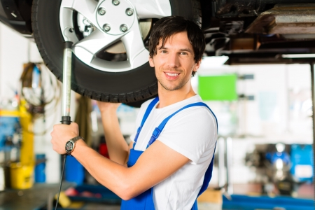blue overall: Young man in blue overall - mechanic - working with lamp on jacked car in a service station Stock Photo