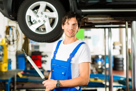 bluey: Young man in blue overall - mechanic - working with lamp on jacked car in a service station Stock Photo