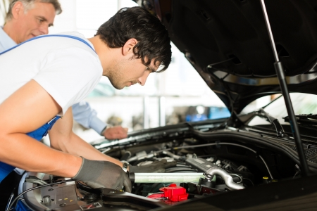 mechanic: Mature client and young mechanic looking under car hood at engine with lamp Stock Photo