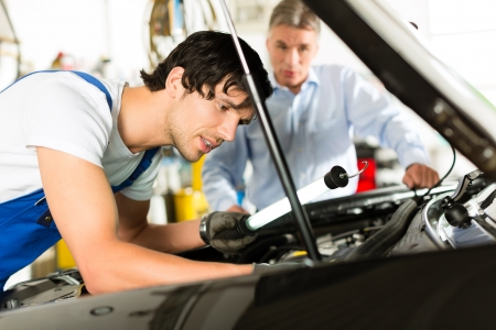 Mature client and young mechanic looking under car hood at engine with lamp Stock Photo - 14727570
