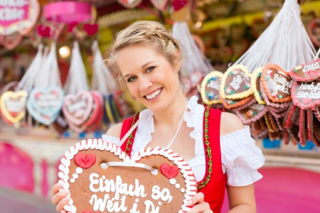 Young woman in traditional Bavarian clothes - dirndl or tracht -with a gingerbread souvenir heart on a festival or Oktoberfest photo