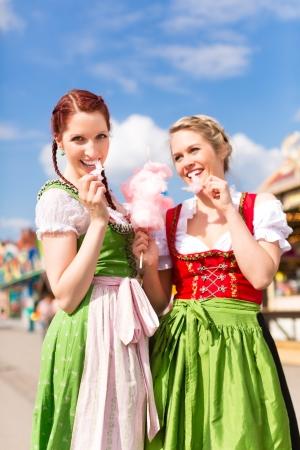 algodon de azucar: Las mujeres jóvenes en ropas tradicionales bávaras - dirndl o Tracht - con algodón de azúcar en un festival o Oktoberfest Foto de archivo