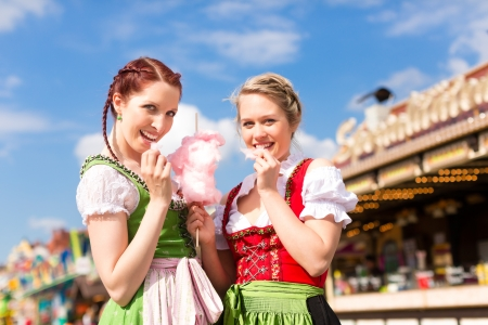 wiesn: Young women in traditional Bavarian clothes - dirndl or tracht - with candyfloss on a festival or Oktoberfest