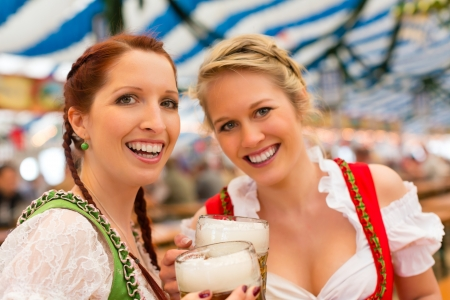 wiesn: Young women in traditional Bavarian clothes - dirndl or tracht - on a festival or Oktoberfest in a beer tent