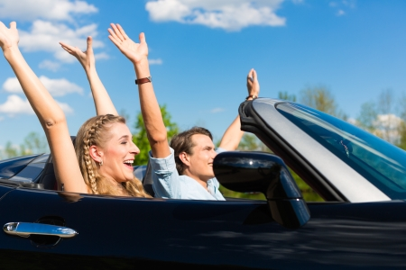 roadster: Young hip couple - man and woman - with cabriolet convertible car in summer on a day trip Stock Photo