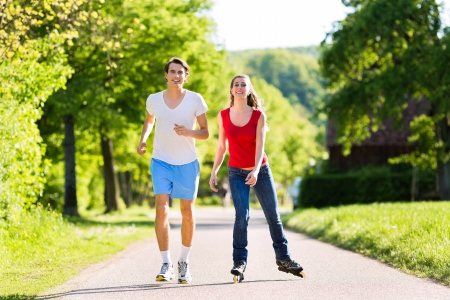 rollerblade: Young couple - man and woman - doing sports outdoors, he is jogging while she is roller blading Stock Photo
