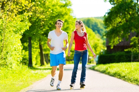 Young couple - man and woman - doing sports outdoors, he is jogging while she is roller blading photo