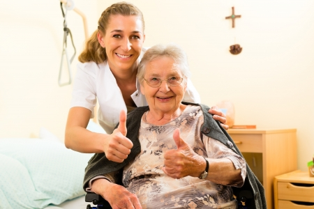 caretaker: Young nurse and female senior in nursing home, the old lady sitting in a wheel chair Stock Photo