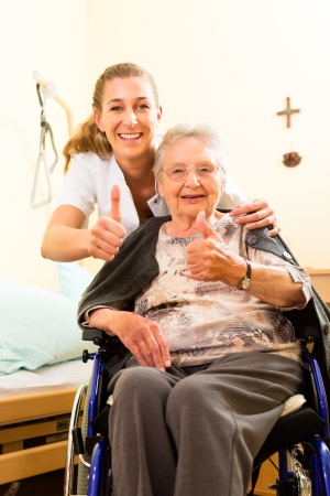 Young nurse and female senior in nursing home, the old lady sitting in a wheel chair photo