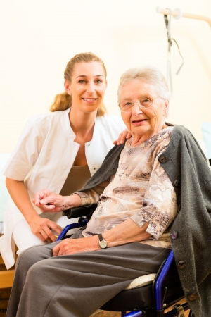 Young nurse and female senior in nursing home, the old lady sitting in a wheel chair Stock Photo - 14727664