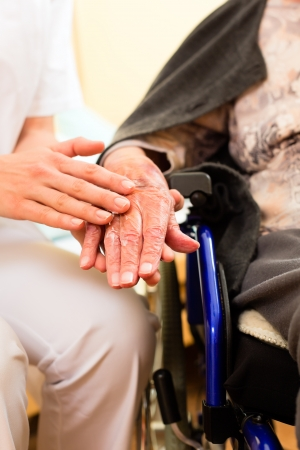 home care: Young nurse and female senior in nursing home, the old lady sitting in a wheel chair Stock Photo