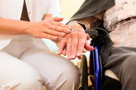 pielęgniarki: Młoda pielęgniarka i kobiet starszych w domu opieki, staruszka siedzącego na wózku inwalidzkim
