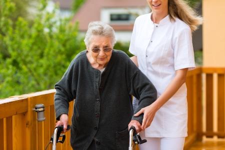 marcheur: Jeune infirmi�re et femme la plus �g�e avec d�ambulateur, le gardien aid�e