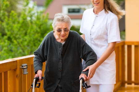 caretaker: Young nurse and female senior with walking frame, the caretaker helping her