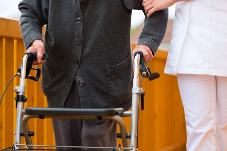 social system: Young nurse and female senior with walking frame, the caretaker helping her