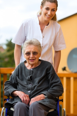 Young nurse and female senior in a wheel chair going for a walk photo
