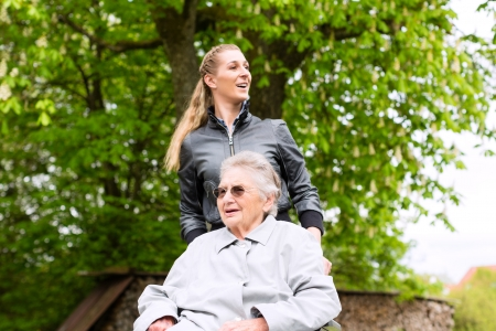 home nursing: Young woman is visiting her grandmother in nursing home having a walk with here in a wheelchair