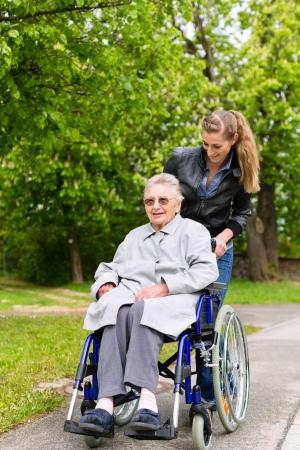 persona en silla de ruedas: Joven mujer se encuentra de visita a su abuela en el asilo de ancianos tiene un paseo con este en silla de ruedas