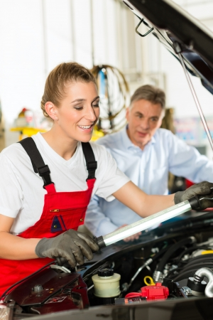 Mature man - client - and young female car mechanic looking under auto hood photo