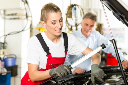 Mature man - client - and young female car mechanic looking under auto hood Stock Photo - 15119923