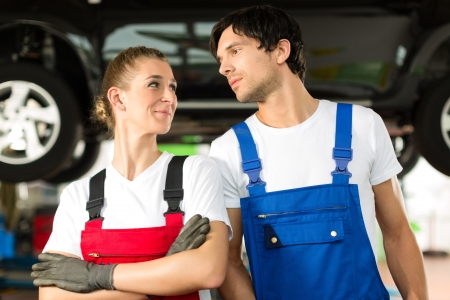 bluey: Young woman and man in blue overall - mechanic - stand with in front of a jacked car in a service station Stock Photo