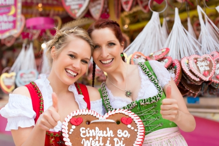 Young women in traditional Bavarian clothes - dirndl or tracht -with a gingerbread souvenir heart on a festival or Oktoberfest photo