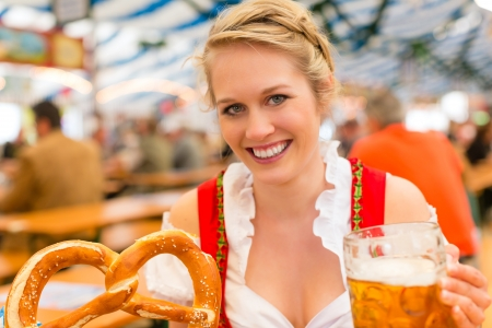 Young woman in traditional Bavarian clothes - dirndl or tracht - on a festival or Oktoberfest in a beer tent