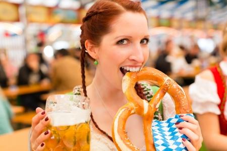 octoberfest: Mujer joven en la ropa tradicional de Baviera - dirndl o tracht - en una fiesta o en una tienda de campaña Oktoberfest cerveza Foto de archivo