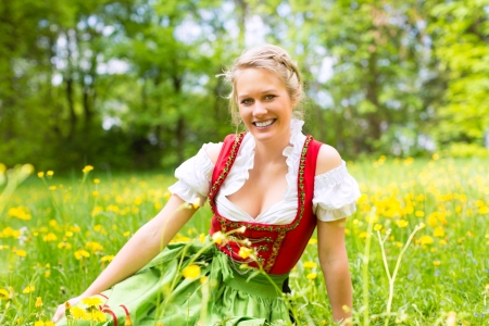 dirndl: Young woman in traditional Bavarian clothes - dirndl or tracht - on a meadow in spring Stock Photo