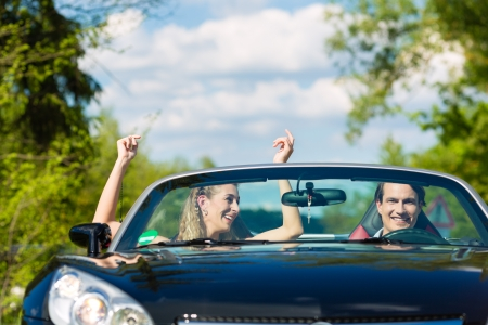 car driving: Young hip couple - man and woman - with cabriolet convertible car in summer on a day trip Stock Photo