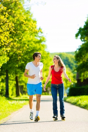 blading: Young couple - man and woman - doing sports outdoors, he is jogging while she is roller blading Stock Photo