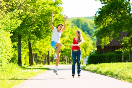 Young couple - man and woman - doing sports outdoors, he is jogging while she is roller blading Stock Photo