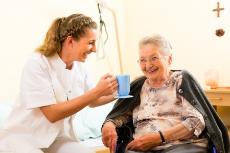 elderly care: Young nurse and female senior in nursing home, the old lady sitting in a wheel chair Stock Photo