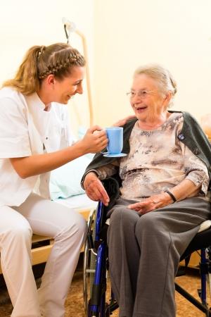 personas ayudandose: Enfermera joven y mujer mayor en hogar de ancianos, la anciana sentada en una silla de ruedas