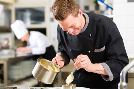 keuken restaurant: Chef-kok in het hotel of restaurant keuken koken, werkt hij aan de saus voor het voedsel als saucier
